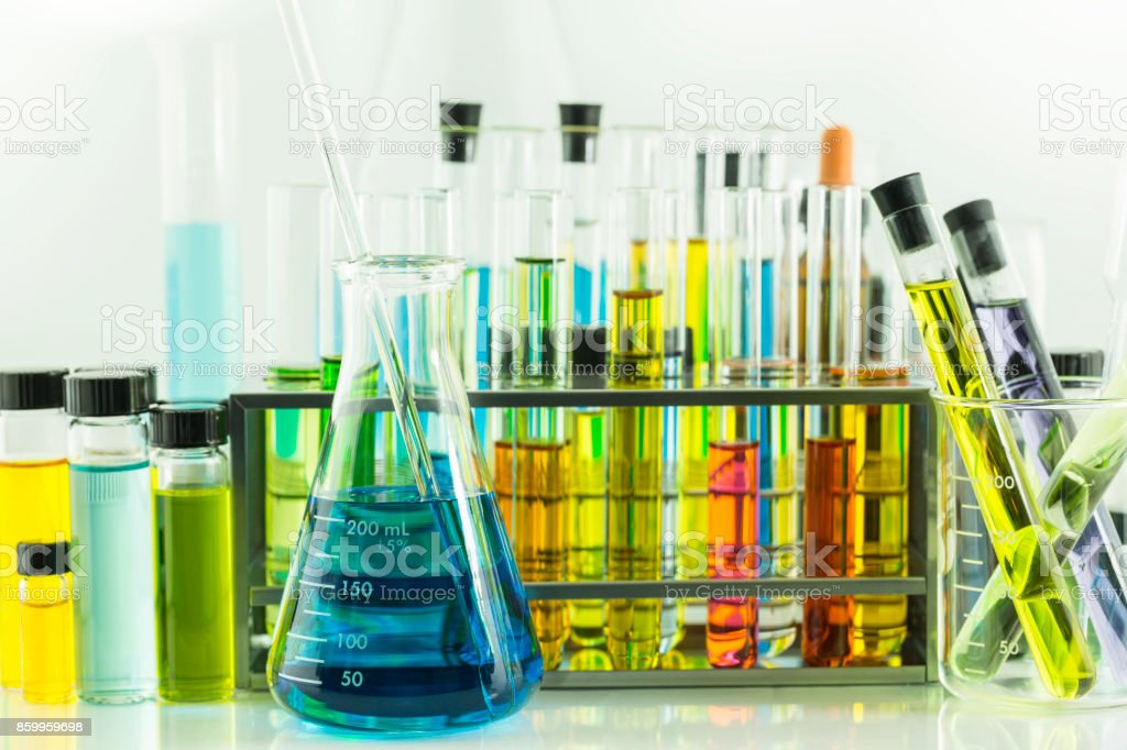 Laboratory glass blue chemical flask and test tubes with colorful...