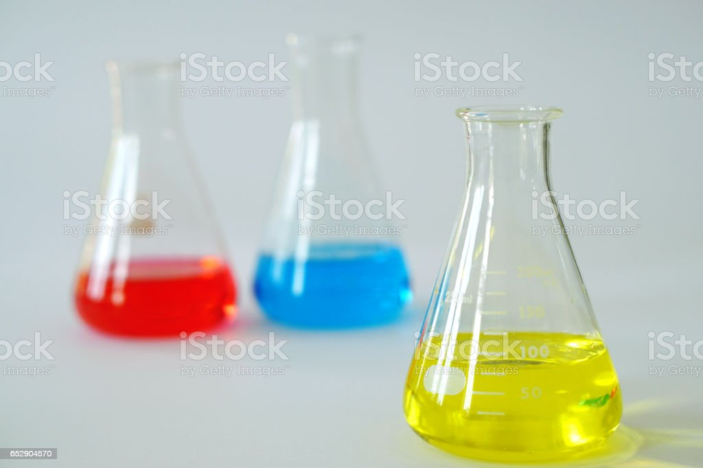 Laboratory glass Erlenmeyer conical flask filled with chemical liquid for a chemistry experiment in a science research lab and copy space. stock photo