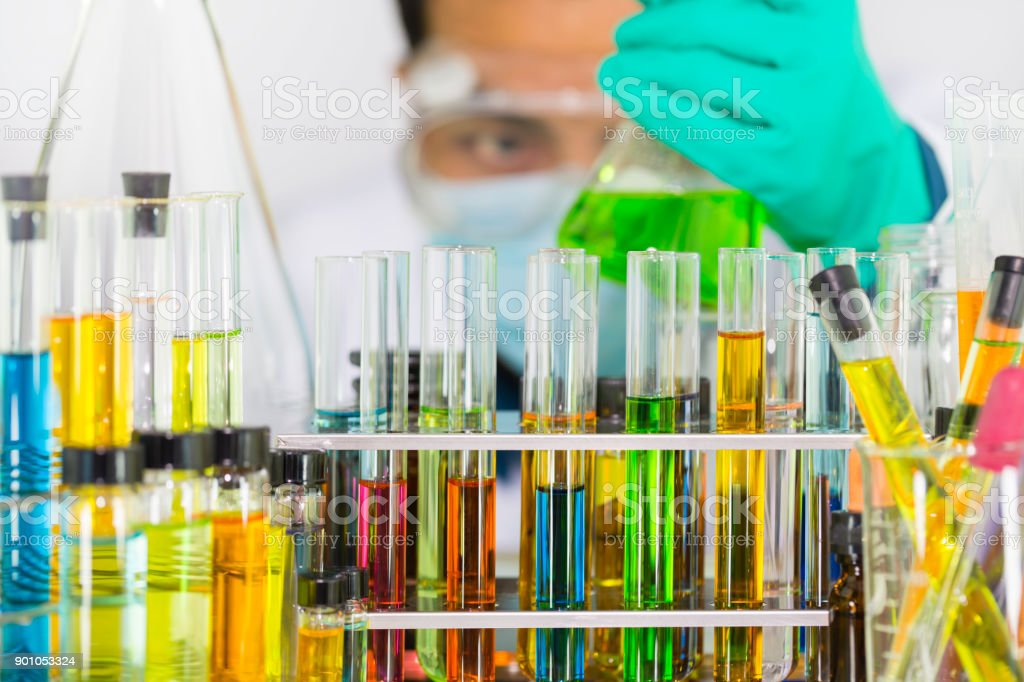 Laboratory glass test tubes and chemical vials with colorful chemical...