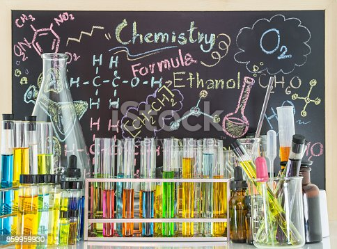 istock Laboratory glass test tubes in test tubes rack and chemical vials with colorful chemical and colorful chemistry formula is written in chalk on the blackboard is the scene behind 859959930