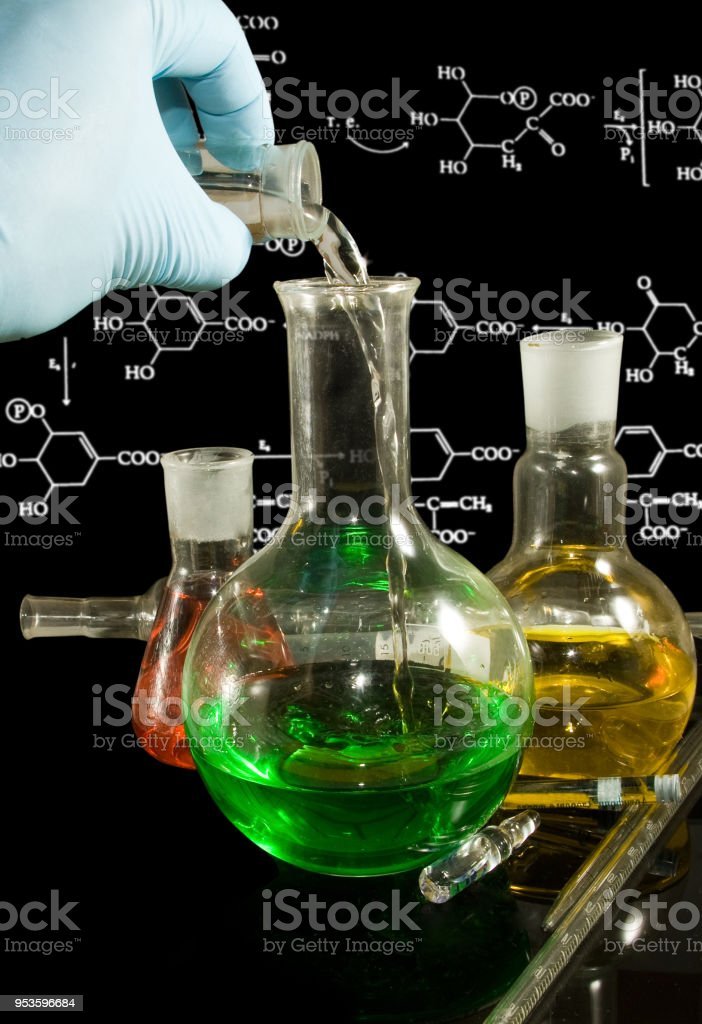 laboratory glassware against the whiteboard with formulas stock photo