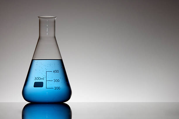 A laboratory measurement flask filled with blue liquid stock photo