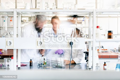 A small group of blurred scientists working in the chemistry lab. Long exposure, focus on the equipment