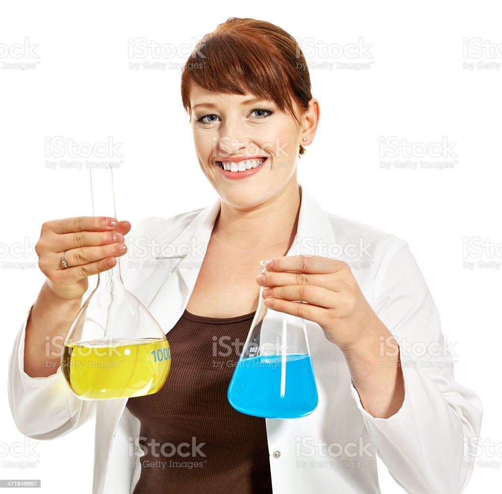 Laboratory Portrait of young laboratory technican holding beakers and smiling at the camera. Studio shot, white background. 20-29 Years Stock Photo