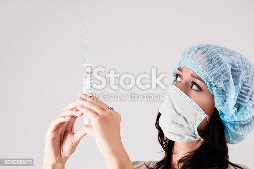 istock Laboratory Staff Holding Syringe Filled with Liquid. Over Gray Background 923068572