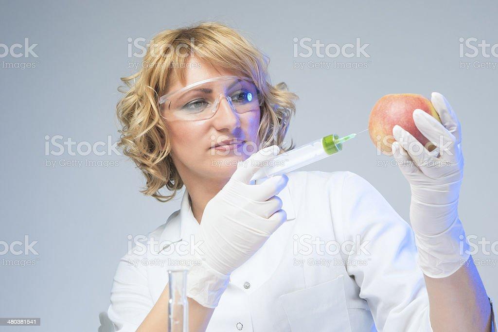 Laboratory Staff Testing Apple Using Syringe royalty-free stock photo