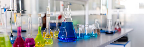 Laboratory table piled tubes with colored liquid Laboratory table piled tubes with colored liquid, colored reagents in flasks and test tubes chemistry class stock pictures, royalty-free photos & images