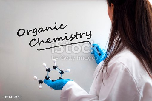 1168035793 istock photo STEM laboratory, teaching science class and female scientist concept with a woman professor in a lab coat, holding chemical molecule in hand, writing on whiteboard with marker pen