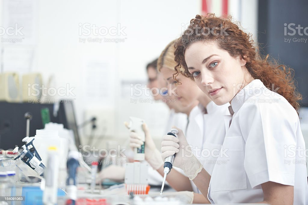 Laboratory technician at work, other scientist on background royalty-free stock photo