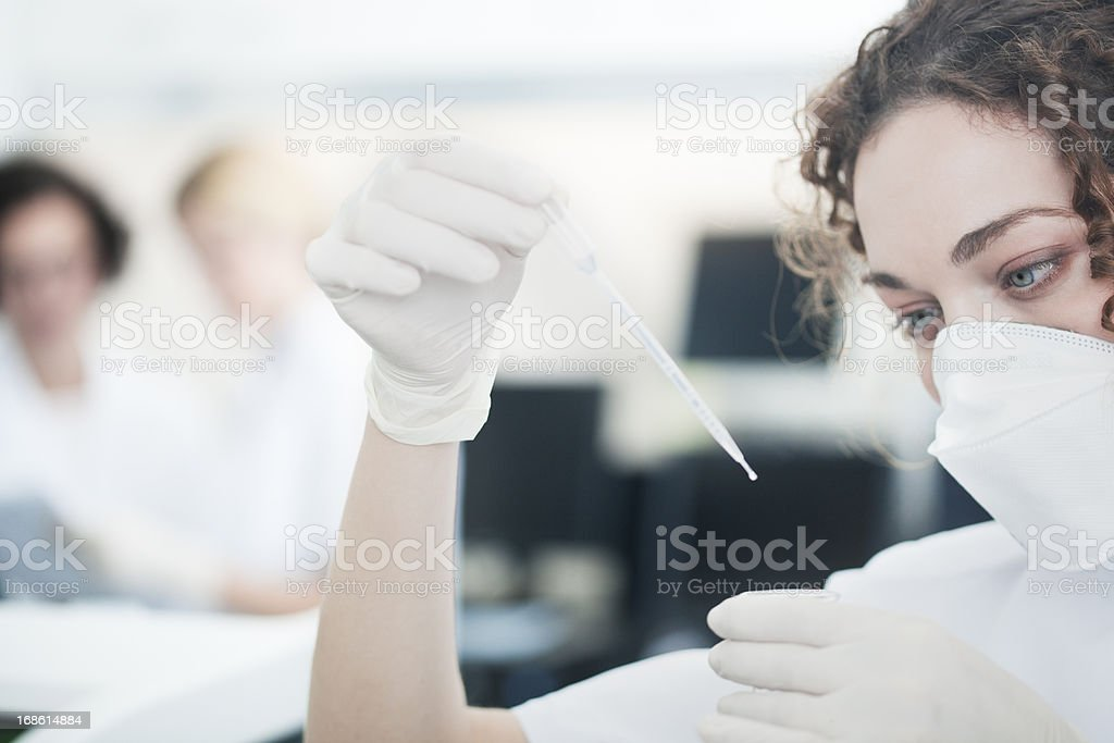 Laboratory technician at work, other scientist on background. royalty-free stock photo