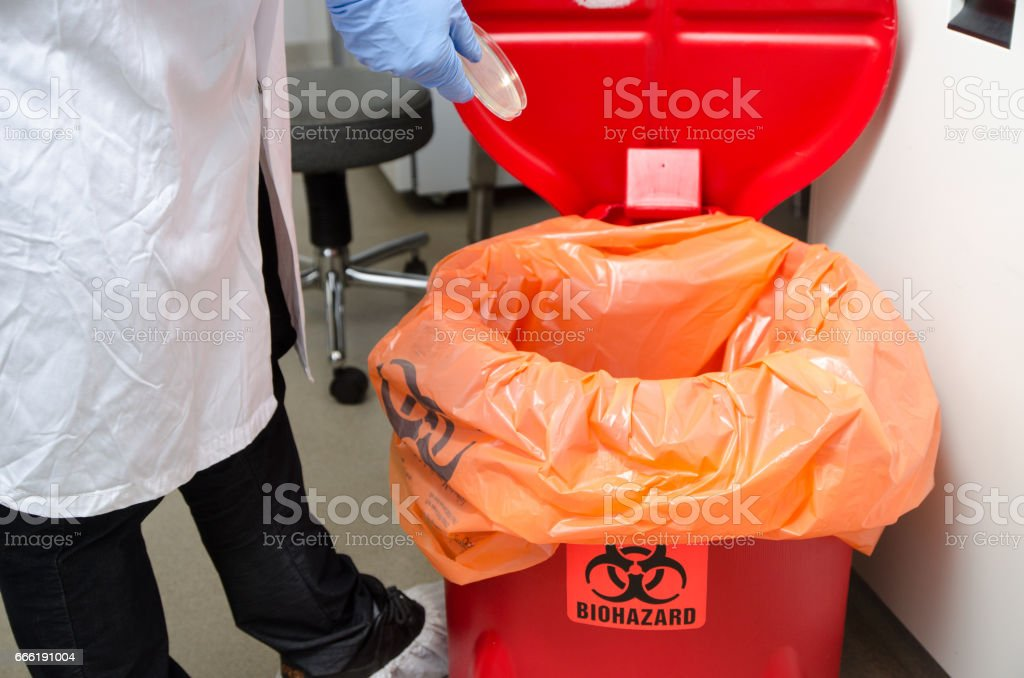 Laboratory worker dropping plastic waste in biohazrd orange trash can stock photo