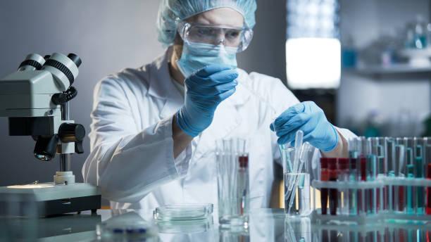 labor-mitarbeiter messen genaue formel für hypoallergen kosmetikprodukte - onkologie stock-fotos und bilder