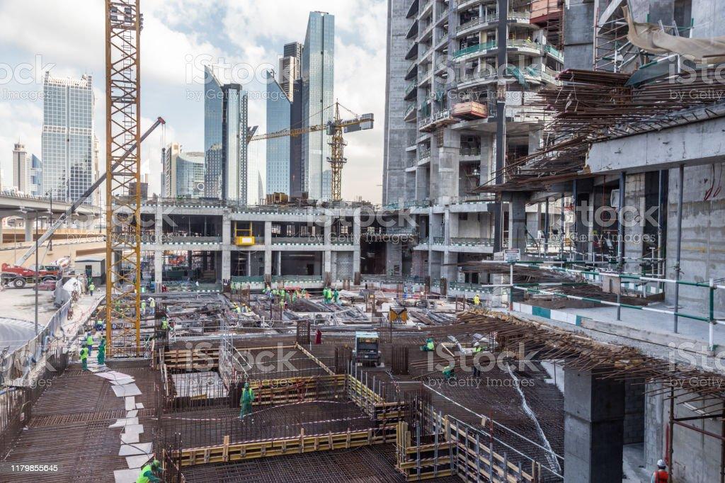 Arbeiter, die an modernen Constraction-Standort arbeiten, arbeiten in Dubai. Schnelle Stadtentwicklung consept - Lizenzfrei Arbeit und Beschäftigung Stock-Foto