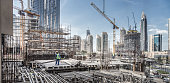 istock Laborers working on modern constraction site works in Dubai. Fast urban development consept 1205700615