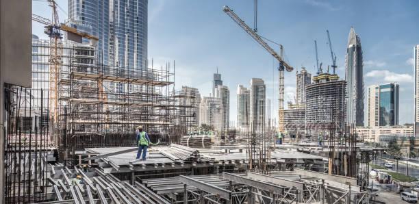 i lavoratori che lavorano sul moderno sito di costruzione lavorano a dubai. contesto di sviluppo urbano rapido - costruire foto e immagini stock