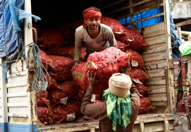 Arbeiter tragen Zwiebelsäcke auf einem Markt – Foto