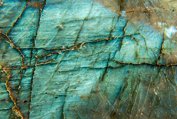 Labradorite Macro with Blue & Auqa iridescence Macro of Labradorite polished specimen with blue and aqua iridescence. Labradorite is a semi-precious stone in the feldspar category. geode stock pictures, royalty-free photos & images