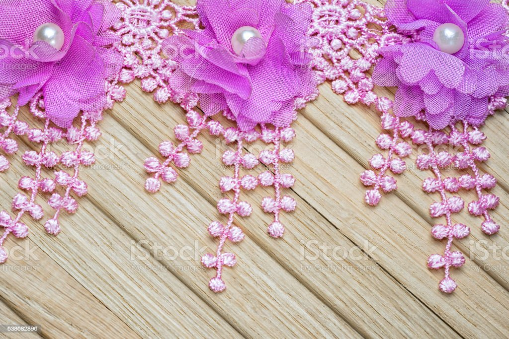 Lace flowers with fringe on a wooden table stock photo