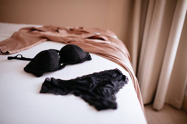 spitzen-dessous und bademantel aus seide auf bett - schwarze romantik stock-fotos und bilder