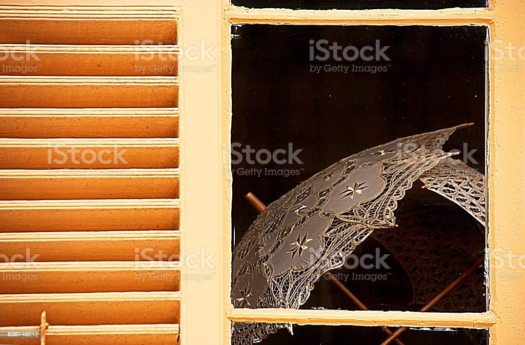 Lace umbrella behind closed window stock photo