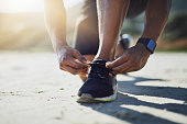 Closeup shot of an unrecognizable man tying his shoelaces while exercising outdoors