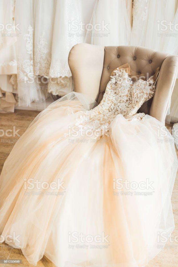 Lace wedding dress on chair in wedding salon stock photo