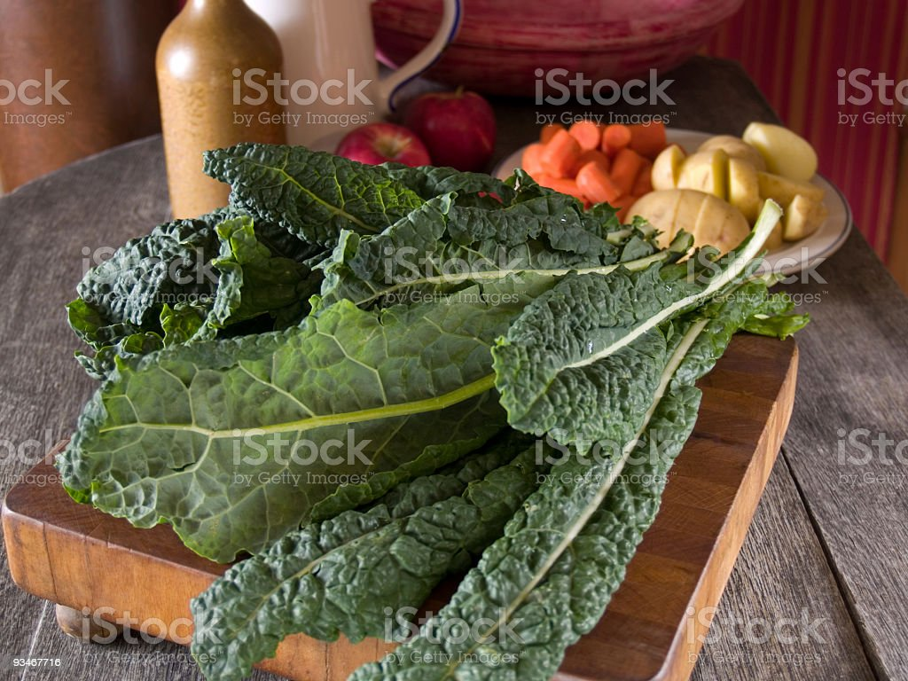 Lacinato kale on cutting board with summer vegetables behind royalty-free stock photo