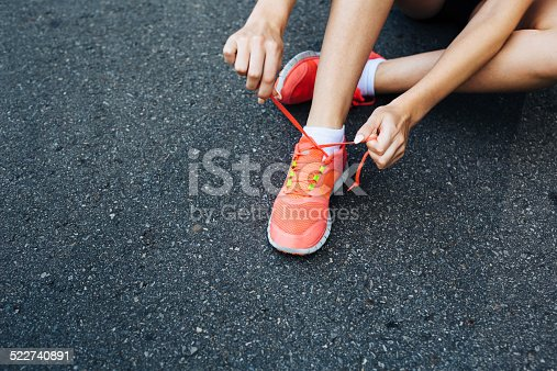 Close-up of a runner lacing her shoes