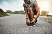Closeup shot of a sporty man tying his shoelaces while exercising outdoors
