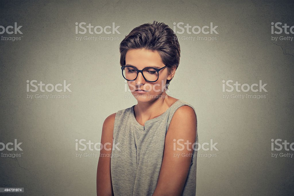 Lack of confidence. Shy woman in glasses feels awkward stock photo