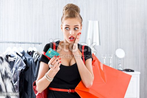 Young adult woman shopping in luxury boutique, worried looking at her credit card.