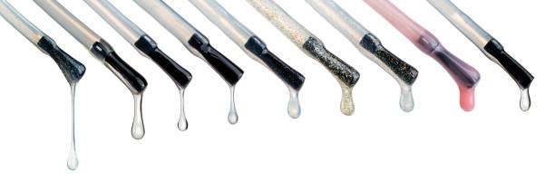 lacktropfen an der spitze der bürste. verschiedene farbige bösartige flüssigkeitstropfen. nagelpflegetechnik, glitzer- und schimmerflüssigkeiten. schöne transparente blobs isoliert auf weiß - rosa glitzer nägel stock-fotos und bilder