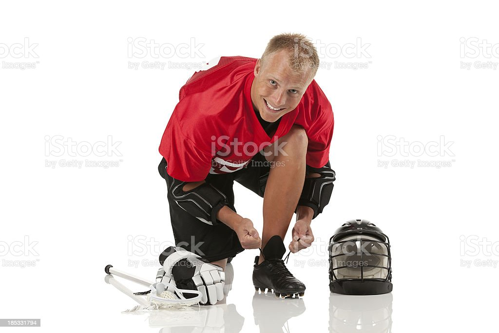 Lacrosse player tying his shoe royalty-free stock photo