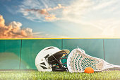 A Lacrosse stick with an orange ball and a B&W helmet sitting on a synthetic grass turf with green padded wall around the sports field and sunbeams from the setting sun.