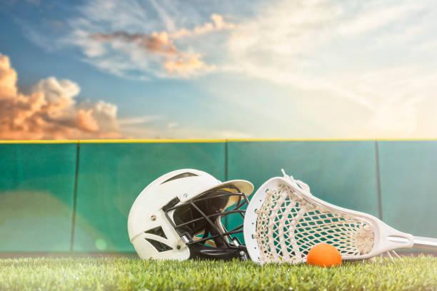 a lacrosse stick, ball and helmet sitting on a synthetic grass turf with sunbeams - kij do gry w lacrosse zdjęcia i obrazy z banku zdjęć