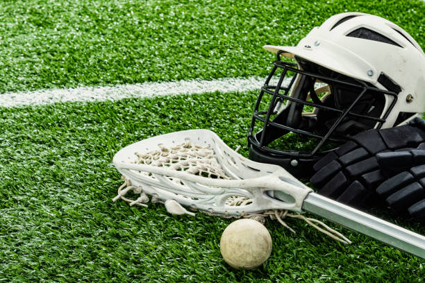 a lacrosse stick, ball, gloves and helmet sitting on a synthetic grass turf - kij do gry w lacrosse zdjęcia i obrazy z banku zdjęć