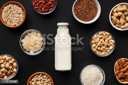 Bowls with various nuts and cereals and bottle of milk top view. Lactose free milk concept