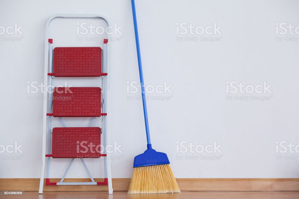 Ladder and sweeping broom stock photo