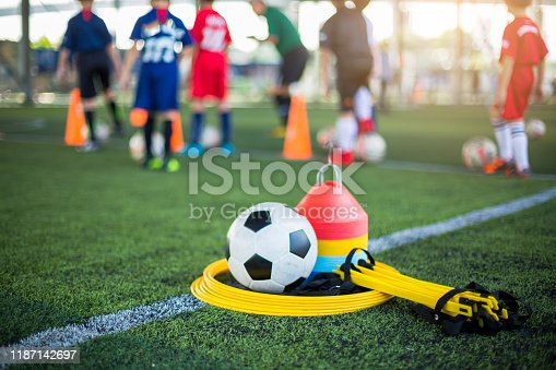 Ladder drills, soccer ball and marker cones on green artificial turf for soccer training equipment.