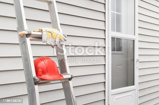 Red hard hat and work gloves on ladder with house siding background.