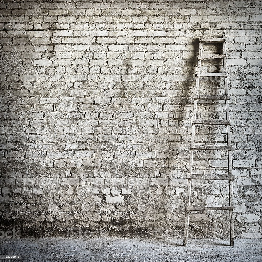Ladder leaning against weathered brick wall royalty-free stock photo