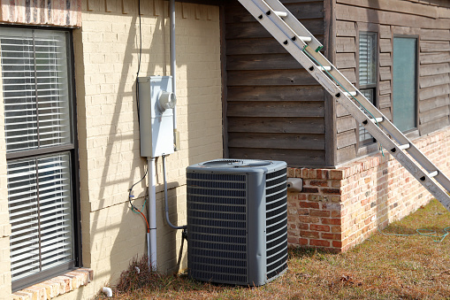 istock Ladder leaning on roof with air conditioner next to house 1089208930