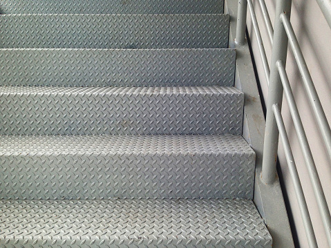 Ladder made of checker plate to increase strength and prevent slipping. Staircase for industrial factory.