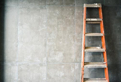 An orange ladder leaning against a grey wall