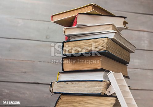 a ladder on pile of old books on wooden background