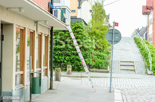 Karlshamn, Sweden - May 06, 2015: Unattended ladder placed on sidewalk against building. Air conditioner being fitted. Nobody in sight.