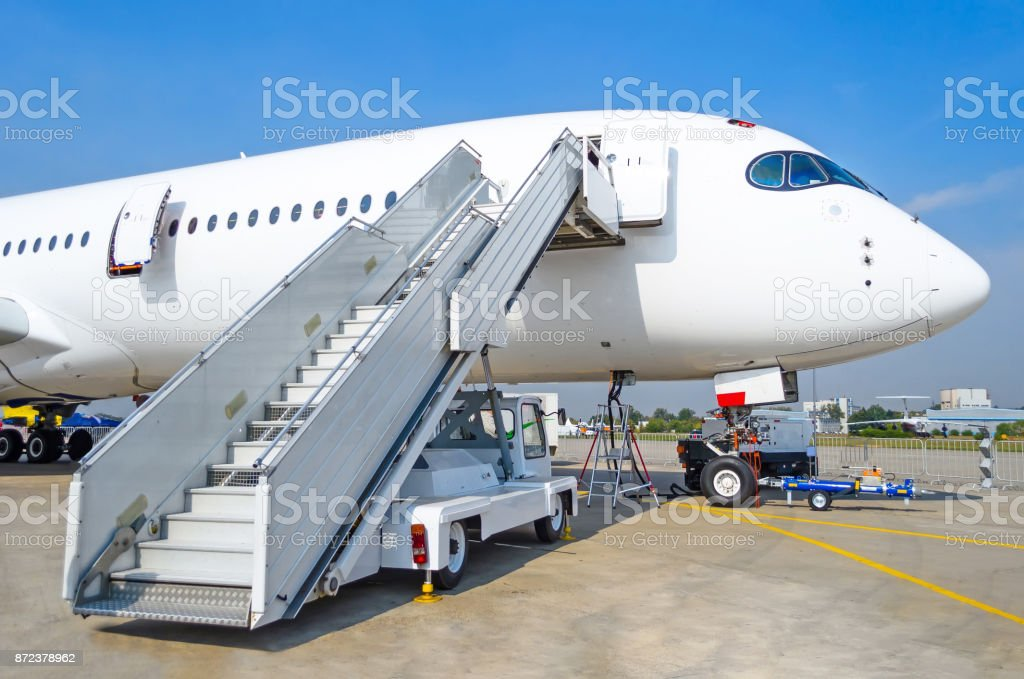 Ladder to the entrance of the aircraft in the parking lot at the airport, view the nose of the aircraft. stock photo