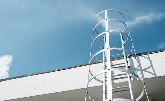 Ladder to the roof of a tall building on blue sky