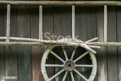 Ladder, wagon wheel and other equipment against a farm shed