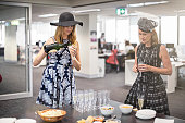 Two Australian women celebrating the Melbourne cup in the office.